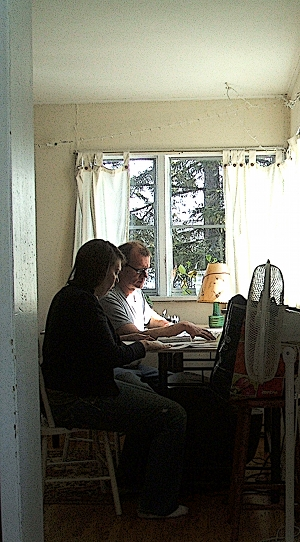 Attila at the little house in the city, showing Terra how to fill out tax returns...