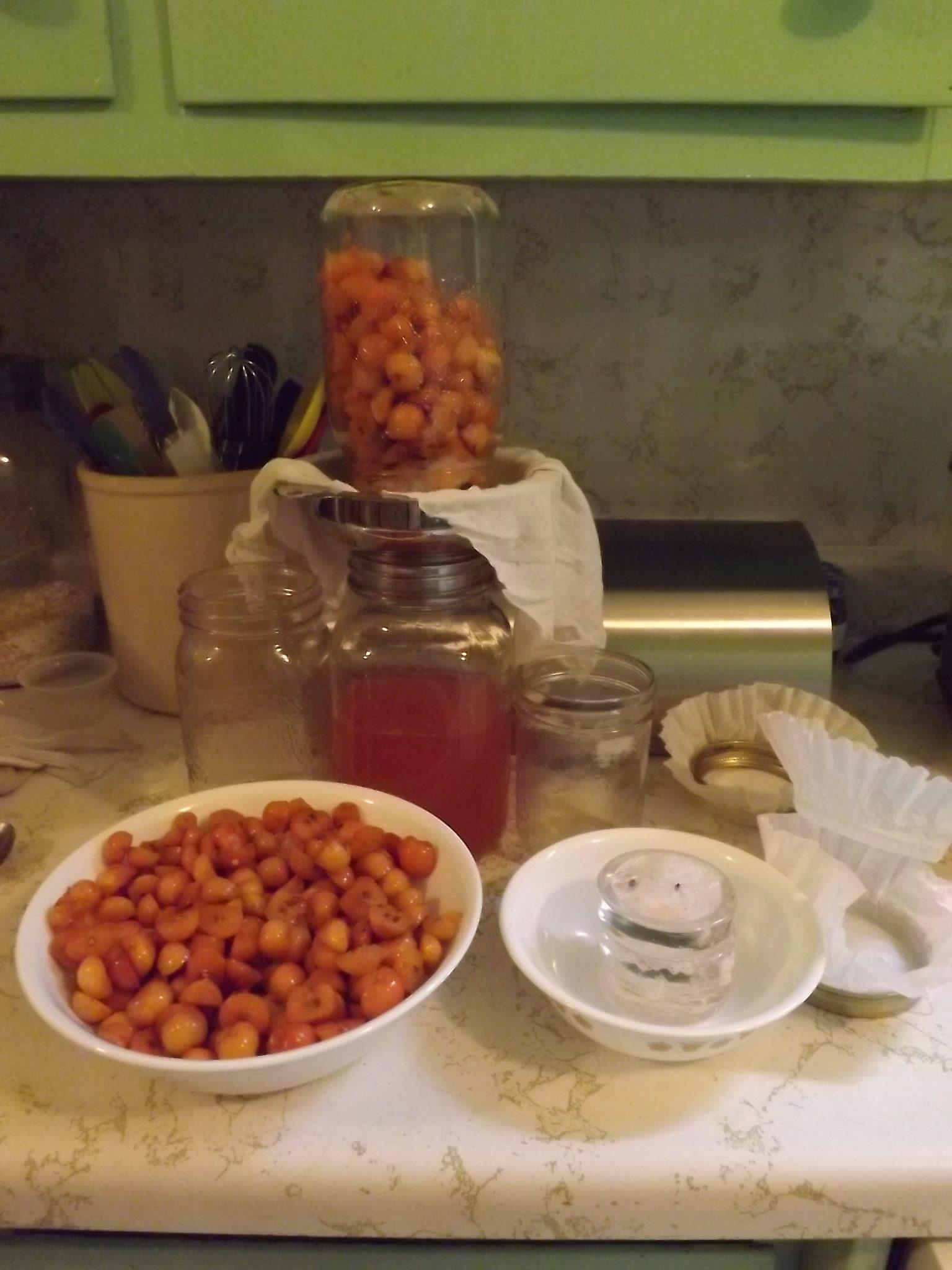 Straining the hard apple cider into a large mason jar.