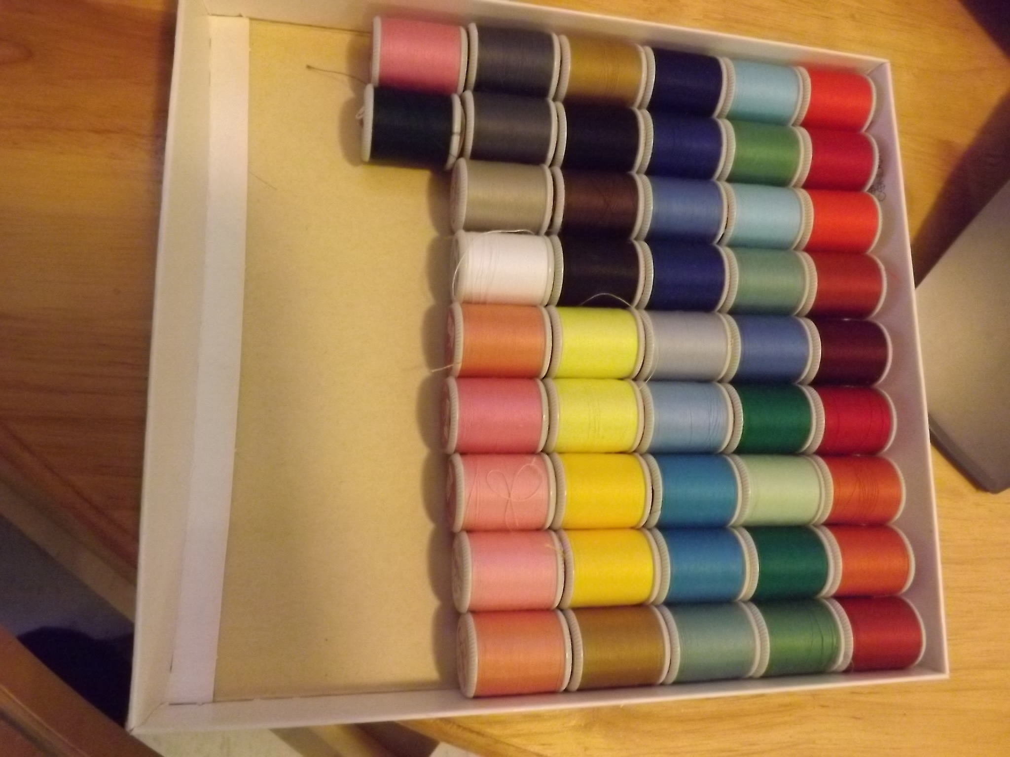 spools of different coloured thread in a box